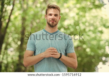 Sportsman inspiring confidence. Handsome sportsman or sports trainer on blurred natural background. Fit sportsman using fitness tracker during training outdoor. Confident sportsman or coach.