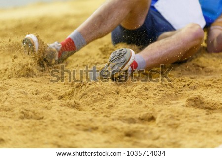 Sportsman landing into sandpit in long jump competition. Track and field competitions concept background #1035714034