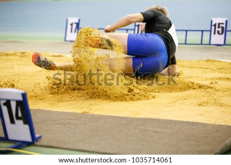 Sportsman landing into sandpit in long jump competition. Track and field competitions concept background #1035714061