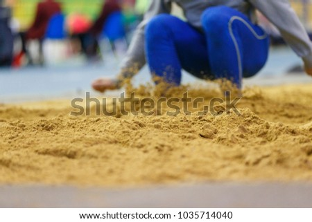 Sportsman landing into sandpit on training in long jump. Track and field competitions concept background #1035714040