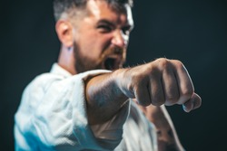 Sportsman martial art taekwondo training, in karate position. MMA - Mixed martial art. Selective focus on fist. Portrait of screaming karate master instructor.