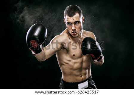 Photo of  Sportsman muay thai boxer fighting in gloves in boxing cage. Isolated on black background with smoke. Copy Space.