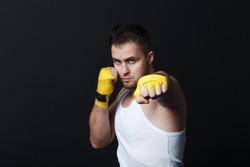 Sportsman muay thai man boxer stance at black background