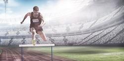 Sportsman practising hurdles against view of a stadium