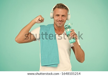 Sportsman promote healthy lifestyle. Happy sportsman on blue background. Fit sportsman with towel. Handsome sportsman flex arm muscle. Drinking water during training. Workout with listening to music.