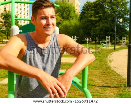 Sportsman relaxing after outdoor workout at street exercise machines for strength exercises. Fit man feeling healthy enjoying sun