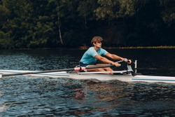 Sportsman single scull man rower rowing on boat. Paddle movement