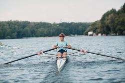 Sportsman single scull man rower rowing technique on boat. Paddle oar splash movement