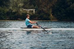 Sportsman single scull man rower rowing technique on boat. Paddle oar splash movement motion