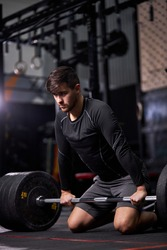 sportsman standing on his knee preparing to make deadlift at gym, young caucasian man in black sportswear engaged in bodybuilding, concentrated on weightlifting. sport, cross fit concept