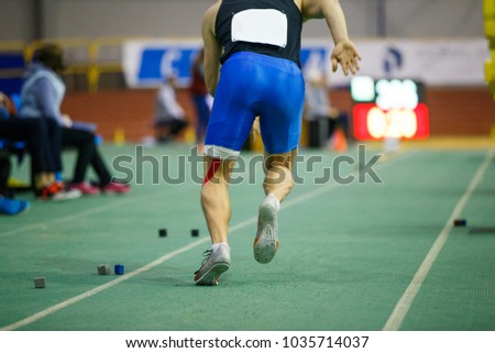 Sportsman starting acceleration in long jump competition. Track and field competitions concept background #1035714037