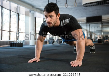 Sportsman wearing blue shorts and black t-shirt doing push-ups #331291745