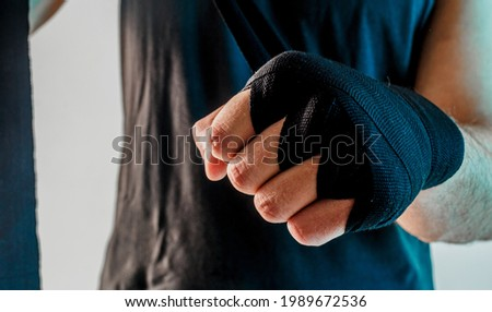 Sportsman wrapping boxing bandage on arm. Close up view. Isolated on turquoise background. Studio shoot Foto stock ©