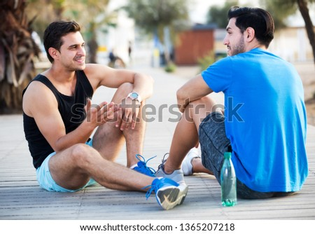 Sportsmen are resting after training and talking about lifestyle in the park near ocean