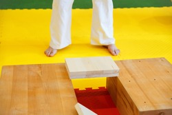 Sportsmen preparing for the competition by breaking wooden boards with his hands in the championship among juniors of the Grodno region Kyokushin karate