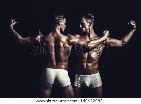 sportsmen with muscular body. sportsmen twins in bodybuilder pose