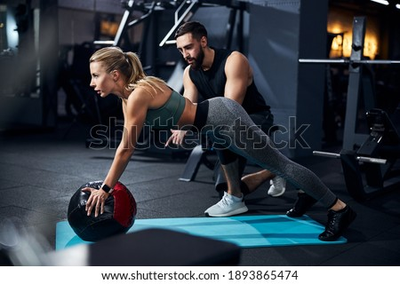 Sportsperson covering a medicine ball with her palms and raising her torso with a coach telling what to do Stok fotoğraf ©