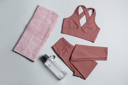Sportswear, bottle of water and towel on grey background, flat lay. Yoga equipment