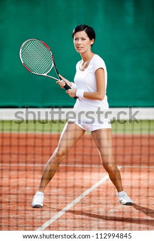 Sportswoman at the tennis court with racquet. Tournament