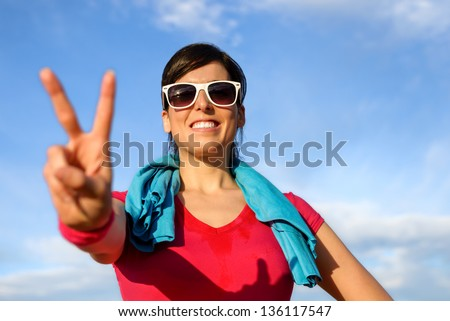Sportswoman celebrating victory and success. Happy fitness woman doing victory symbol with her hand on sky background. Girl sweating after training and exercising. - stock photo