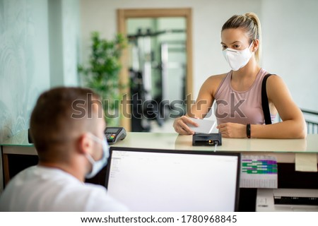 Sportswoman checking with smart phone at health club reception desk while wearing protective face mask.