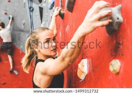Sportswoman climber moving up on steep rock, climbing on artificial wall indoors. Extreme sports and bouldering concept ストックフォト ©