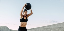 Sportswoman doing intense workout with medicine ball. Muscular woman screaming while exercising with medicine ball outdoors.
