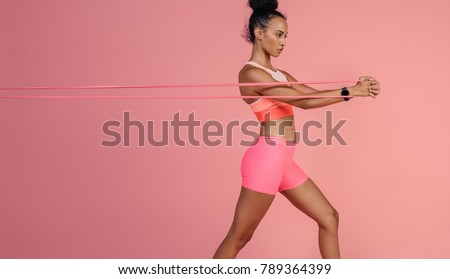 Sportswoman exercising with resistance band. Female with working out with elastic band on pink background.