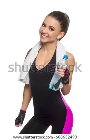 Sportswoman holding bottle of water. Smiling girl dressed in dark sportswear took a break to quench thirst. Drinking to prevent dehydration.