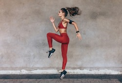 Sportswoman jumping and stretching. Full length of healthy female exercising and jumping outdoors.