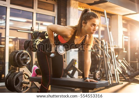 Sportswoman lifting weights in gym.