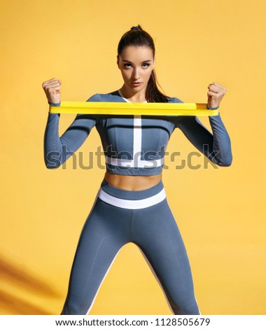 Sportswoman performs exercises for the muscles of the hands. Photo of woman workout with resistance band on yellow background. Strength and motivation. #1128505679