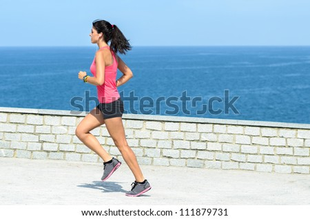 Sportswoman running outdoors on blue sea background. Caucasian brunette young model exercising on summer day.