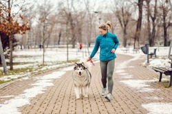 Sportswoman running with her dog in a park on cold winter day. Pets, winter fitness, runner, togetherness