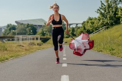 Sportswoman training in the park and running with a resistance parachute tied behind her