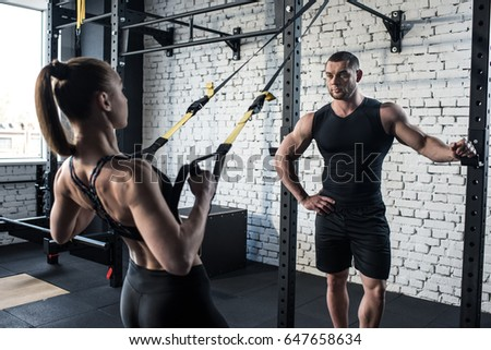 sportswoman training with trx resistance band with serious trainer in sports center