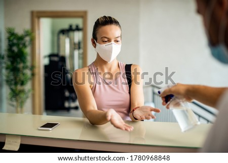 Sportswoman wearing protective face mask while receptionist in disinfecting her hands at the gym.