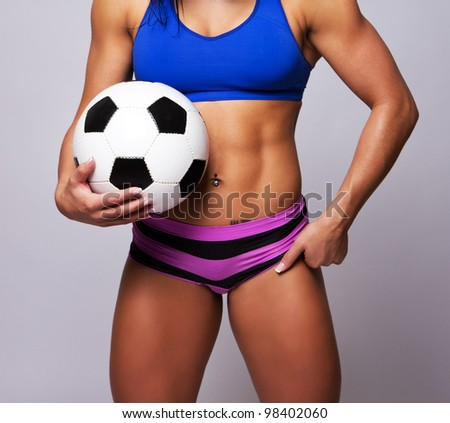 Sportswoman with ball on black background