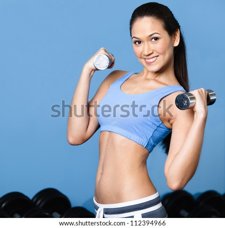 Sportswoman works out with dumbbells in gym class