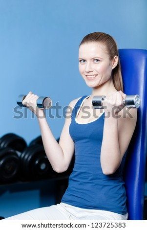 Sportswoman works out with dumbbells in training gym