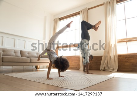 Sporty active african american family father and kid daughter doing handstand at home, healthy parent black dad with cute little child girl enjoy leisure gymnastic activity playing together at home
