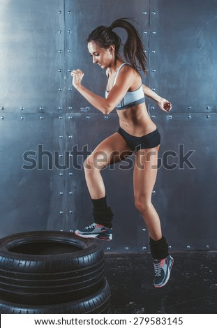 Sporty active fit woman box jumping. Female athlete is performing tire jumps fitness, sport, training and lifestyle concept