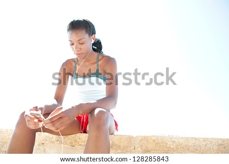 "Sporty ""african american"" woman sitting and getting ready for exercise, listening to music with her mp4 player against a bright blue sky."