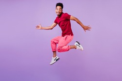 Sporty african guy in red casual t-shirt relaxing during photoshoot. Positive male model with short black hair jumping on purple background.
