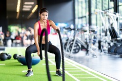 Sporty asian woman exercising with battle ropes at the gym on green floor. Strong female determine with her indoor workout for stamina and building muscular body. Athlete battle rope workout concept.