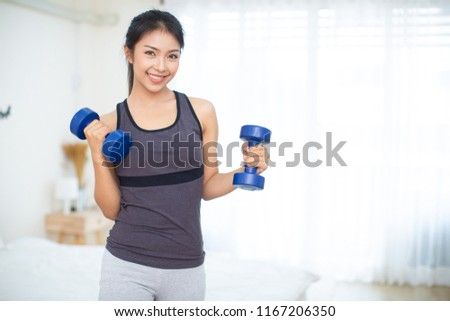 Sporty beautiful woman exercising with dumbbell at home to stay fit