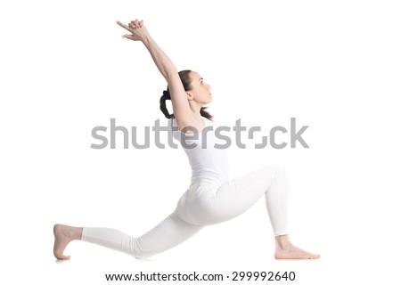 Sporty beautiful young woman doing low lunge exercise, variation of anjaneyasana, ashwa sanchalasana, horse rider pose, profile view, studio full length shot, isolated