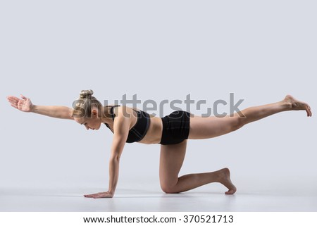 Sporty beautiful young woman practicing yoga, doing balance exercise bird dog, kneeling opposite arm and leg extension, asana sunbird (chakravakasana), working out wearing black sportswear, studio