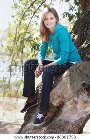 Sporty blue-eyed smiling woman sitting on a tree against blurred background with selective focus