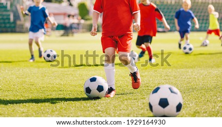 Sporty children on football summer camp. Kids practicing football on grass field. Football soccer children training class. Group of school children running and kicking soccer balls on training camp